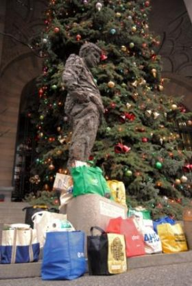Mayor Caliguri looking over offerings of food in totes near the official City-County Christmas Tree, November 2011