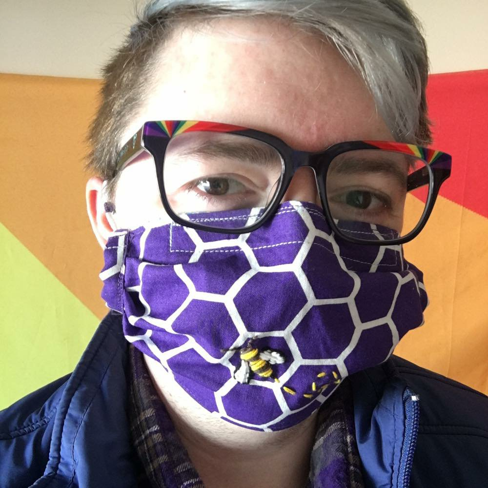 person with short hair wearing a purple face mask